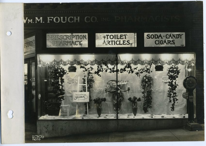 Window display of the Wm. M Fouch Company, Inc., Pharmacists store on E. 36th Street, Baltimore, 1925.  Note the large penny scale outside the doors at right.  Anonymous gift. JMM1998.47.19.1