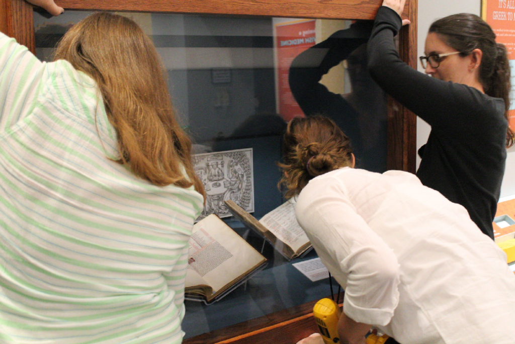 Collections Manager Joanna Church took care of the page-turning itself, but the process also needed the assistance of interns Tamara and Gina, who helped took off and put back the sealed case fronts, and Cade, who documented our progress.